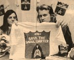 """Chuck Cook and Doris Gove with a T-Shirt Reading """"Save the Snail Darter"""" by Jed DeKalb"""